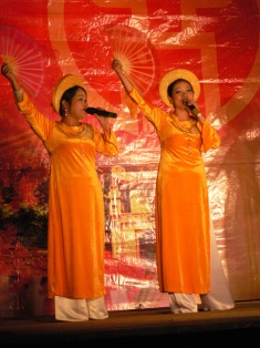 Performers of Tet (Lunar New Year) entertainment wear traditional Ao Dai. These events are held all around town on the streets in temporary stages set up for that purpose. People of all ages perform for large local crowds.