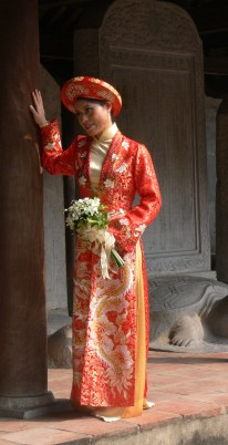 Silk brocade wedding Ao Dai, complete with circular headgear called a khăn đóng is worn. Wedding photos were taken at the Temple of Literature (Van Mieu).