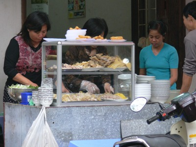 Chicken restaurant with all cooked chicken bits, nothing is ever wasted in Vietnam. Hanoian customers drive up on motorbike, park, get served, sit on plastic chairs outside, some inside seating is available.