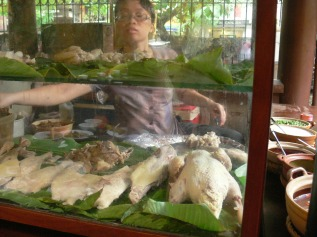 Boiled chicken in display cabinet as staff prepares a dish for the next customer at Quan An Ngon Restaurant, Hanoi.