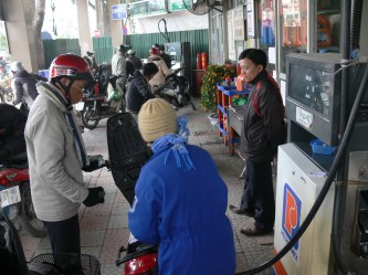 On a cold Hanoi day, this fuel attendant fills up guy, once done push bike out of the area, be well away from stand before you start your bike.