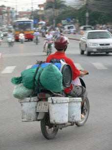 Vietnamese motor bike rider is loaded up but still prepared to take on oncoming cars is his style. Hanoi, Vietnam.
