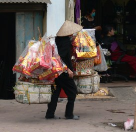 Lady Vietnamese street vendor walks the streets of Hanoi carrying special Tet paper votive's that will be burnt to send to the Kitchen God, Hanoi, Vietnam.