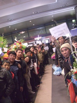 Noi Bai Airport, Hanoi. Tet 2010 - Eager family members crowd the exit of the airport arrivals waiting for the first glimpse of their loved ones who often ONLY come home once a year.