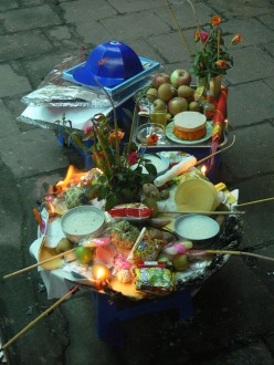 This offering table is to honor the anniversary of a young person's death. It is not so formal and has flowers, fruit, food, snacks, rice, candles and incense burning, alcohol, cigarettes, lighter, sweets and the votive hat is one with a Nike sticker on it, Hanoi, Vietam