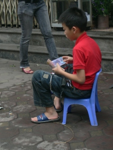 Young Vietnamese boy helps his Dad burn votive offerings - sending money (not real money), Hanoi, Vietnam