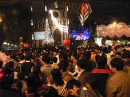 Crowds enjoy the festive feeling and televised service, Nativity scene to the right outside Hanoi Cathedral, Nhà Chung, Hanoi, Vietnam.