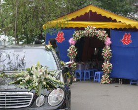 Wedding tent - all dressed up and waiting for the bride and groom and party goers ! Beautifully prepared including car with bouquet of flowers taped to it. In Hanoi, tents pop up, parked on the road since personal garden space is limited.