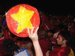 Vietnamese Football Supporter holds a fan painted as the National flag.