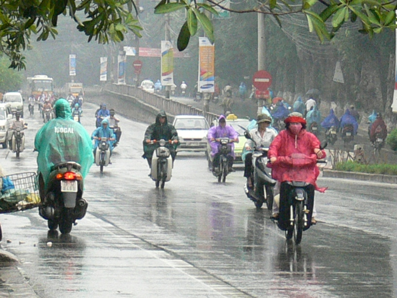 2008 photo - rain in Hanoi never stops progress. Biker put on rain coat that accommodate one or 2 people.