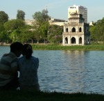 Young people out on a date, the Turtle Tower on Hoan Kiem Lake, Hanoi, Vietnam makes a romantic backdrop.