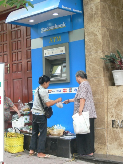 101 uses of an ATM step - this enterprising vendor displays her wares on the step you would normally stand on to use the ATM. Hanoi, Vietnam.