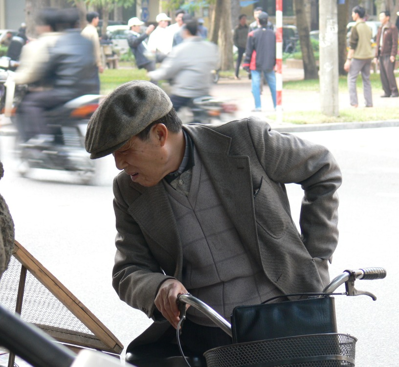 Vietnamese man looks for luck Lottery numbers off his bicycle, Hanoi, Vietnam.