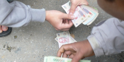 Vietnamese men counting Vietnamese money together.