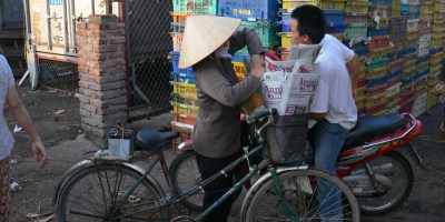3. Newspapers For Sale while working in the Long Bien Market riding past on motorbike stops as a newspaper seller on her bike - notice that she has a battery strapped on the back (on carrier), as while she drives around an announcement is repeated telling people she has newspapers for sale. Hanoi, Vietnam.