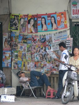 Seller takes a nap, while customer catches up on the news - 2010, Hanoi, Vietnam.