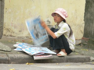 Young newspaper sales girl. She sorts the newspapers out, then she will head off on her rounds selling them on the streets, in cafes and in business's door to door, Hanoi, Vietnam.