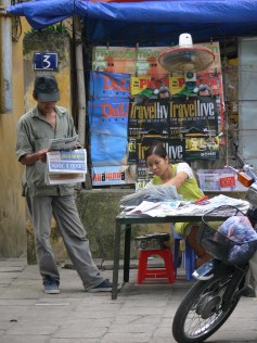 Standing up at the small stall, vendors don't seem to mind if locals have a quick read.