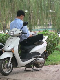 Now we are talking !! Comfort plus, plus !! Reading: Balanced sitting on a motorbike crossed-legged reading a newspaper. Hanoi, Vietnam.