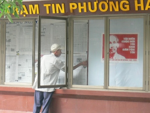 This gentleman's job is to hang up the daily newspaper in this public display; so anyone can read the paper for free. Hanoi, Vietnam.