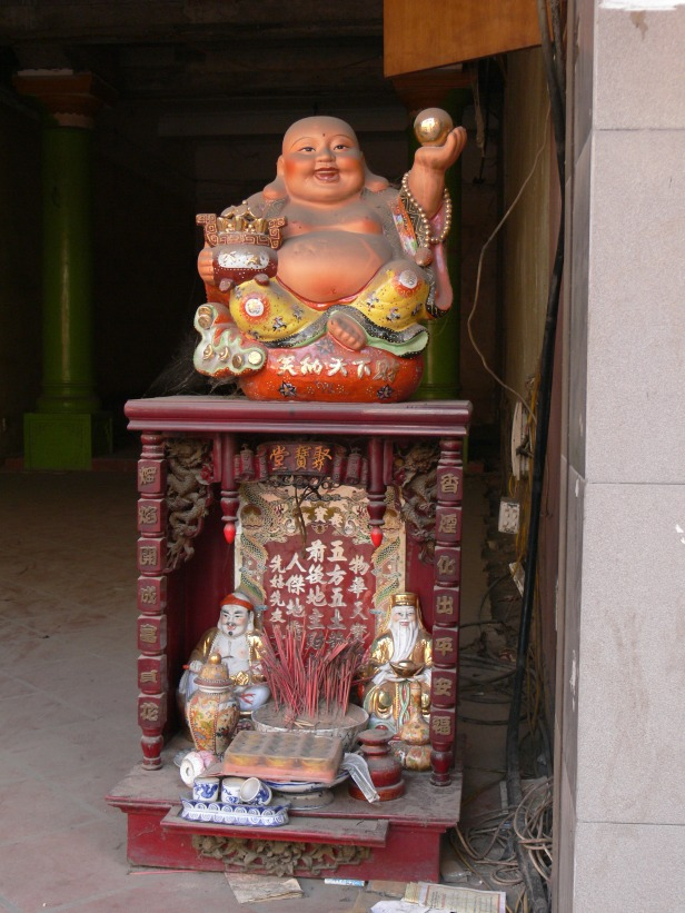 Smiling Buddha on top welcoming happiness and below is the spirit house for the land spirits, in Hanoi City, Vietnam.