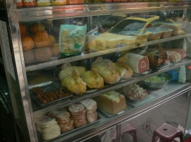 Pressed meats, pates, salamis and smoked chicken displayed at grocer at 17-19 Ly Quoc Su Street, Hanoi (2010).
