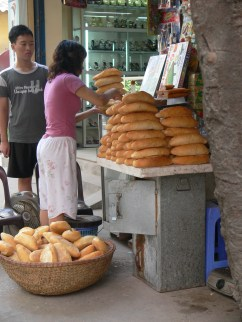 Fresh french bread is readily available on the streets of Hanoi. often still hot, as kept warm in small charcoal powered ovens.
