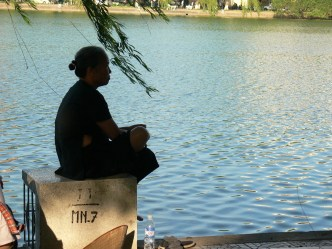 A Vietnamese woman takes time for contemplation on a summers day , beside Hoan Kiem Lakeside, Hanoi, Vietnam