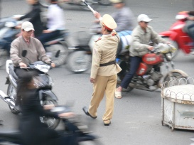 Poor Vietnamese Policeman tries his best to keep everyone going in the right direction. He has a mission on his hands, but slowing the rules are being adhered to. (pre 2007 helmet law).