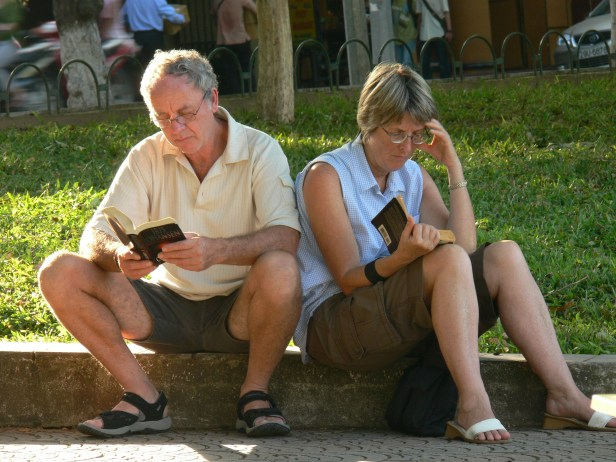 Before smart phones tourist enjoy sitting by Hoan Kiem Lake, Hanoi, Vietnam reading a book.
