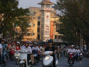 Cruising around on motorbikes in Hanoi + Thang Long Water Puppet Theater in the background, at the North End of Hoan Kiem Lake, Hanoi.