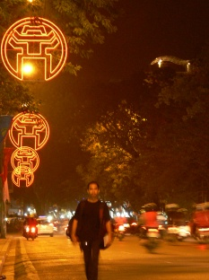 Hanoi city logo lights the streets at night. Vietnamese man walks around town with hundreds of Hanoi logo in neon lights.