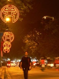 Hanoi city logo lights the streets at night. Vietnamese man walks around town with hundreds of Hanoi logo in neon lights.