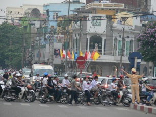 It's rush hour and everyone is in a rush to get home. Officer is on crowd control duties. Vietnamese Policeman tries to direct the traffic in Hanoi.