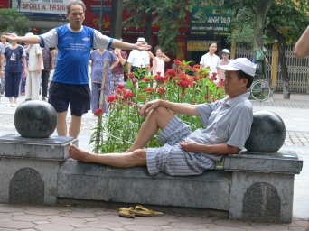 Don't mind me ! One Vietnamese man sitting relaxing and another doing Thai Chi, in park near Water Tower, Hanoi