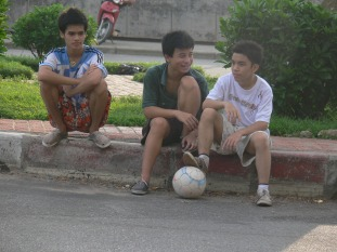 Three Vietnamese boys out for an early morning footy game near Water Tower Hanoi.