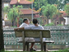 Two Vietnamese gentlemen sit on a bench overlooking Tran Quoc Temple on West Lake, Hanoi, Vietnam.