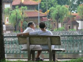 Two Vietnamese gentlemen sit on a bench overlooking Tran Quoc Temple on West Lake, Hanoi, Vietnam.