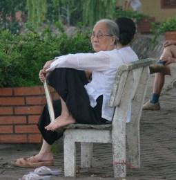 A Vietnamese woman takes a quiet break, hot morning - fan in hand !