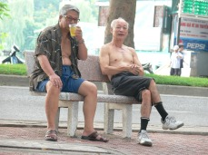 Two Vietnamese gentlemen sit and chat after exercising, Yes, I know it looks like beer but its iced tea.