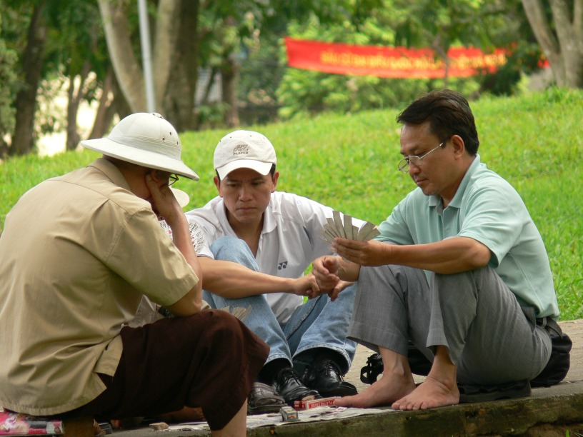 Ummm !! How shall I play this ??? Vietnamese men play a Chinese card game in a park in Hanoi.
