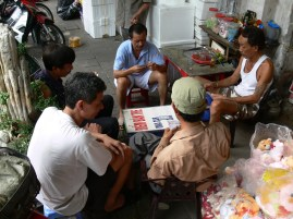 Taking a break from busy business duties, guys play cards and drink some tea in Hanoi Old Quarter.