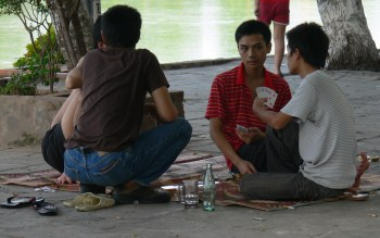 You're bluffing aren't ya ?? Two Vietnamese young men play cards by Chuc Bach Lake, Hanoi.