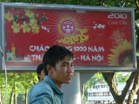 2010 poster celebrating Hanoi 1000 years with Vietnamese man standing in front of it.