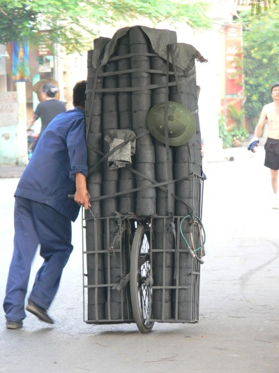 1. Starting off the day having to push their cart with about 300 little charcoal rounds for either delivery or selling their own charcoal is hard work. At the end of the day the guys must feel so free while biking home, Hanoi, Vietnam.