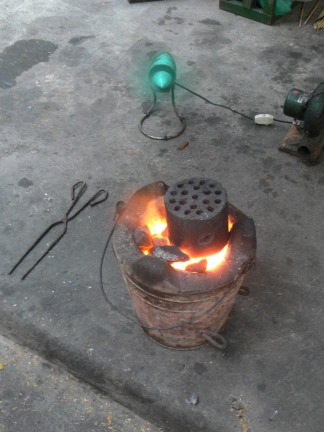 4. Charcoal-round cooker heating up, its on, now the wood just has to burn down and the round slot into the hole. As the wood burns down the charcoal-round slots into the bottom of the stove. All of this is assisted with the fan to get it moving faster, Hanoi, Vietnam.