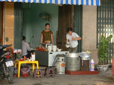 2010 photo - Gas and charcoal rounds are being used together. Gas for quick cooking and charcoal for long slow burning items, in Noodle Shop, Hanoi, Vietnam.