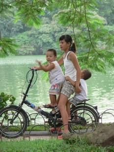 There's enough room for everyone - 3 children share one bike beside Hoan Kiem Lake, Hanoi.