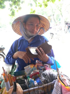 Vietnamese street vendor - And . . . oh yeah and I have this wallet on sale, just for today.