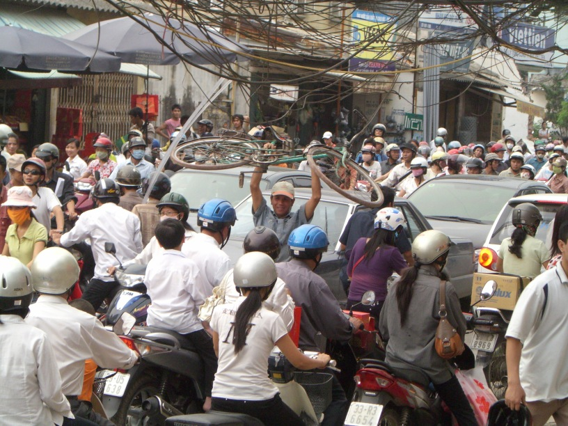 It's a traffic jam from hell !! A complete gridlock, the old road at Lac Long Quan, Hanoi was being upgraded and everyone wants to get home. Luckily the guy on the bicycle can carry his bike through the masses to get out of this mess.